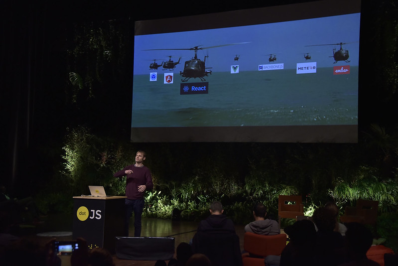 Adrian Holovaty in front of the giant screen showing a picture of heavy helicopters with a logo of many frameworks on top of them